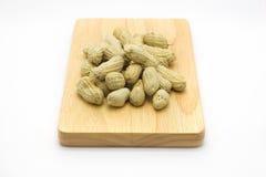 Cacahuetes blancos de la placa de madera en el top Imagenes de archivo