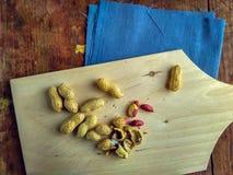 Cacahuetes en la tabla de cortar de madera, aún vida en estilo del vintage Fotografía de archivo