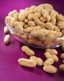 Cacahuetes en un fondo púrpura Imagen de archivo libre de regalías