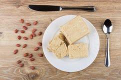 Cacahuetes, pedazo de halva del cacahuete en placa, cucharilla y cuchillo fotos de archivo