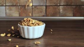 Cacahuetes que vierten en un plato blanco en la tabla de madera almacen de video