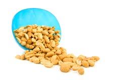 Cacahuetes salados que caen del tazón de fuente azul Fotos de archivo