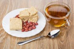 Cacahuetes y pedazos de halva del cacahuete, de té y de cucharilla fotos de archivo