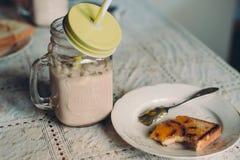 Cacao avec du lait dans le pot et des pains grillés à la table de cuisine image stock