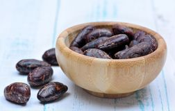Cacao beans in a bamboo bowl on table stock photo