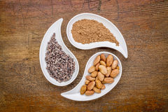 Cacao beans, nibs and powder. Raw cacao beans, nibs and powder - top view of teardrop shaped bowls against rustic wood royalty free stock photography