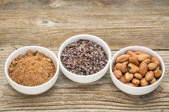 Cacao beans, nibs and powder. In white ceramic bowls against grained wood royalty free stock image