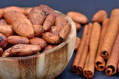 Cacao beans in a wooden bowl with cinnamon sticks stock photos
