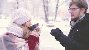 Cacao caldo laughthing e bevente di conversazione e felice dell'uomo barbuto e della bella ragazza dalle tazze in loro mani nell' stock footage
