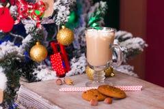 Cacao caliente con las melcochas en la tabla vieja en fondo de la Navidad Foto de archivo