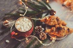 cacao caliente con las melcochas y el cruasán en la tabla de madera rústica con las luces de la Navidad Imagenes de archivo