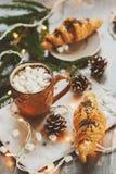 cacao caliente con las melcochas y el cruasán en la tabla de madera rústica con las luces de la Navidad Fotos de archivo