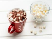 Cacao caliente y un puñado de melcochas en un bol de vidrio imagen de archivo