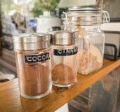 Cacao, cannella, zucchero in bottiglie di vetro. Fotografia Stock Libera da Diritti