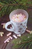 Cacao chaud dans une tasse grise avec des guimauves sous l'arbre de Noël Images stock
