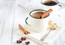 cacao chaud savoureux avec des bâtons de cannelle sur le fond en bois blanc photos stock