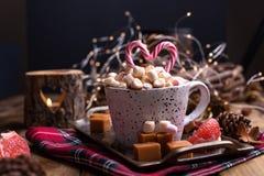 Cacao con las melcochas en una taza blanca, diversos caramelos de la Navidad y dulces Foto en estilo oscuro y espacio libre para  imagen de archivo libre de regalías