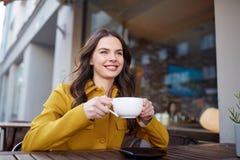 Cacao de consumición de la mujer feliz en el café de la calle de la ciudad Imagen de archivo