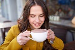 Cacao de consumición de la mujer feliz en el café de la calle de la ciudad Foto de archivo libre de regalías
