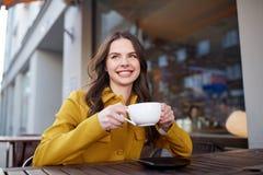 Cacao de consumición de la mujer feliz en el café de la calle de la ciudad Imágenes de archivo libres de regalías