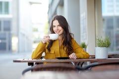 Cacao de consumición de la mujer feliz en el café de la calle de la ciudad Fotos de archivo
