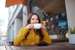 Cacao de consumición de la mujer feliz en el café de la calle de la ciudad Imagenes de archivo