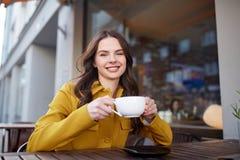 Cacao de consumición de la mujer feliz en el café de la calle de la ciudad Fotografía de archivo libre de regalías