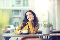 Cacao de consumición de la mujer feliz en el café de la calle de la ciudad Fotografía de archivo