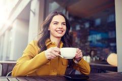 Cacao de consumición de la mujer feliz en el café de la calle de la ciudad Fotos de archivo libres de regalías