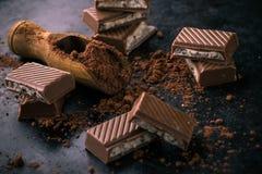 Cacao en cuchara de madera en la bandeja oscura con el chocolate_ Imagen de archivo libre de regalías