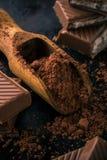 Cacao en cuchara y pocos pedazos de chocolate Imagen de archivo libre de regalías