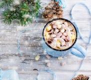 Cacao en la taza azul, regalos, abeto, conos del pino, en el de madera viejo Fotos de archivo libres de regalías
