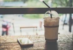 Cacao helado, chocolate, con crema del azote en taza plástica y teléfono móvil en la tabla de madera imágenes de archivo libres de regalías