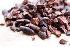 Cacao nibs close up. Cacao nibs on the light wooden surface - macro close up shooting Royalty Free Stock Image