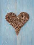Cacao nibs shaped in heart symbol. Organic cacao nibs shaped in a heart on a wooden table Stock Photo