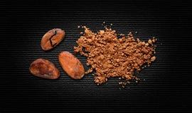 Cacao in polvere delle fave di cacao su carta nera Immagini Stock Libere da Diritti