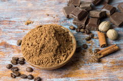 Cacao powder in a bowl with chocolate and cinnamon royalty free stock image