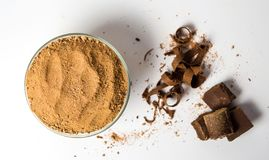 Cacao powder in a bowl and chocolate slices on white stock photography