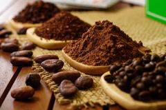 Cacao powder, cocoa nibs, and coffee beans on wooden plates on burlap. Background stock photos