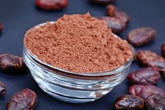 Cacao powder in a transparent bowl with beans on blue background stock image
