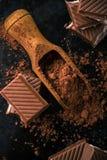 Cacao y pocos pedazos de chocolate con el relleno cremoso Imagen de archivo libre de regalías