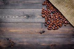 Cacaobonen dichtbij canvas op de donkere houten ruimte van het achtergrond hoogste meningsexemplaar Stock Foto