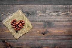 Cacaobonen op canvas op de donkere houten ruimte van het achtergrond hoogste meningsexemplaar Stock Afbeeldingen