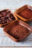 Cacaobonen, poeder en geraspte chocolade in houten kommen Royalty-vrije Stock Fotografie
