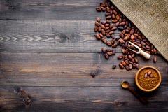 Cacaopoeder dichtbij cacaobonen en canvas op de donkere houten ruimte van het achtergrond hoogste meningsexemplaar Stock Afbeeldingen