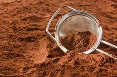Cacaopoeder met zeef stock foto