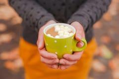 Cacau doce com o marshmallow nas mãos fêmeas Foto de Stock