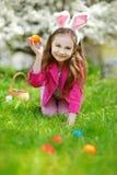 Caccia adorabile della bambina per l'uovo di Pasqua sul giorno di Pasqua Immagini Stock