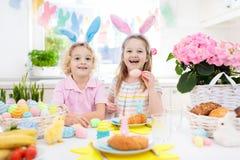 Caccia dell'uovo di Pasqua Bambini con le orecchie ed il canestro del coniglietto fotografie stock libere da diritti