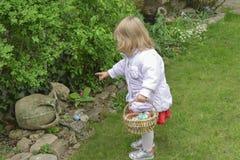 Caccia della bambina per l'uovo di Pasqua in un giardino della molla fotografia stock libera da diritti